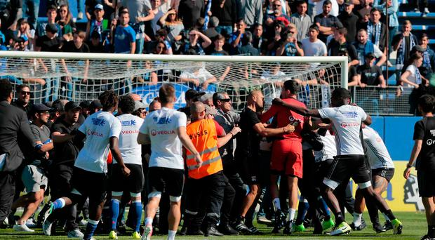 Bastia's supporters invade the pitch to try to fight with Lyon's Portuguese goalkeeper Anthony Lopes (in red)