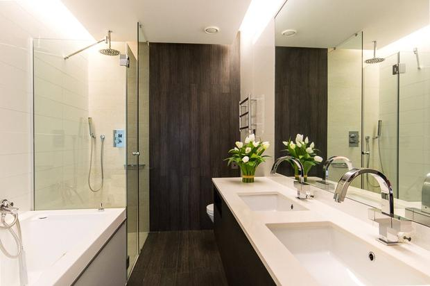 The fully tiled master en suite includes a bath and power shower