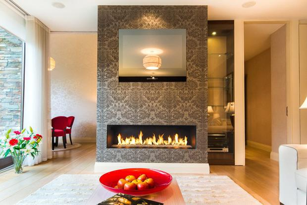 The open plan living/dining room features a gas fire set in natural stone