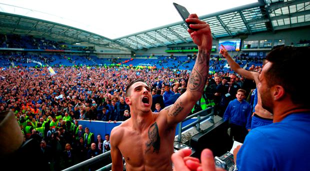 Anthony Knockaert takes a picture to capture the scene after Brighton fans invaded the pitch to celebrate promotion to the Premier League. Photo: GETTY