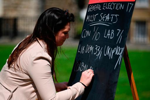 A betting company employee writes odds on a blackboard outside London's Houses of Parliament Picture: AFP/Getty