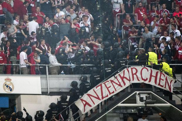Riot police clash with Bayern fans in the tribunes during the UEFA Champions League quarter-final second leg football match Real Madrid vs FC Bayern Munich at the Santiago Bernabeu stadium in Madrid in Madrid. Photo: CURTO DE LA TORRE/AFP/Getty Images