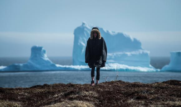 A resident views the first iceberg of the season as it passes the South Shore, also known as