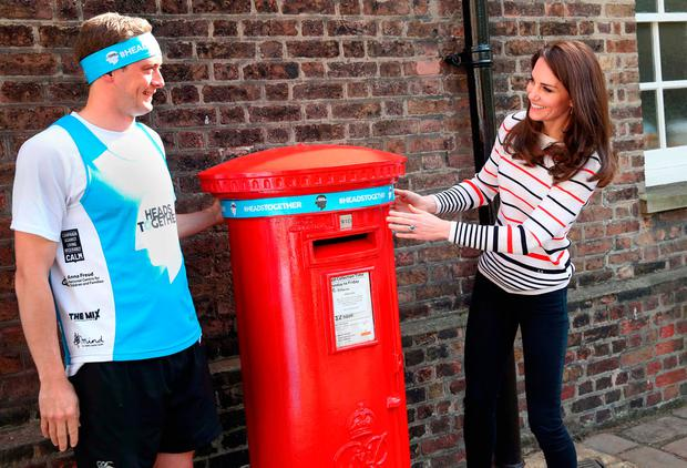 Britain's Catherine, Duchess of Cambridge, together with runner Alex Stanley, puts a Heads Together headband onto the Kensington Palace post-box ahead of a reception for Team Heads Together, at Kensington Palace on April 19, 2017 in London