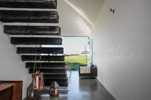 Louise McGuane and Dominic McCarthy's Co Clare cottage: A staircase made from old railway sleepers leads way to the couple's comfortable bedroom Photo Credit: RTE