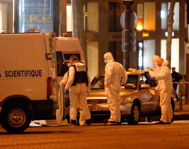 Forensic experts collect evidences from the car belonging to an attacker who killed a police officer on the Champs Elysees avenue in Paris, France, Friday, April 21, 2017. An attacker with an automatic weapon opened fire on (AP Photo/Thibault Camus)