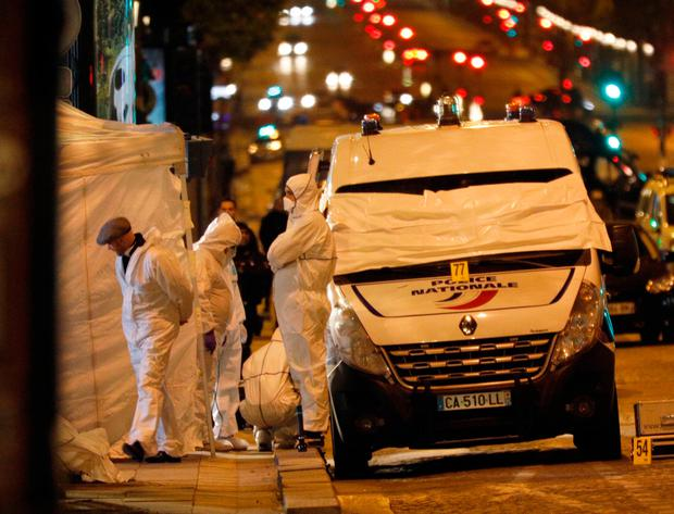 Forensic experts investigate the crime scene after a fatal shooting in which a police officer was killed along with an attacker on the Champs Elysees avenue in Paris, France, Friday, April 21, 2017. (AP Photo/Kamil Zihnioglu)