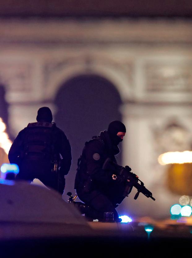 Masked police stand on top of their vehicle on the Champs Elysees Avenue after a policeman was killed and two others were wounded in a shooting incident in Paris, France, April 20, 2017. REUTERS/Christian Hartmann