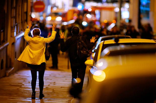 People raise their arms to show their hands as they walk towards police on a side road near the Champs Elysees Avenue after a policeman was killed and two others were wounded in a shooting incident in Paris, France, April 20, 2017. REUTERS/Benoit Tessier