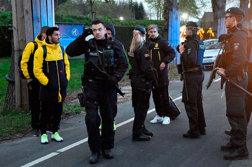 Dortmund's Marcel Schmelzer, third from right, talks to police officers outside the team bus after it was damaged in an explosion before the Champions League quarterfinal soccer match between Borussia Dortmund and AS Monaco in Dortmund, western Germany. (AP Photo/Martin Meissner, file)