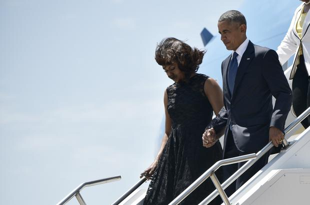 US President Barack Obama and First Lady Michelle Obama step off Air Force One hand-in-hand.. / AFP / MANDEL NGAN (Photo credit should read MANDEL NGAN/AFP/Getty Images)