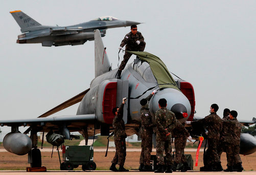 South Korean Air Force soldiers cover a F-4E Phantom fighter jet as a US Air Force F-16 Fighting Falcon fighter jet takes off in the background during the Max Thunder Air Exercise at a US air base in Gunsan, South Korea. Photo: SeongJoon Cho/Bloomberg