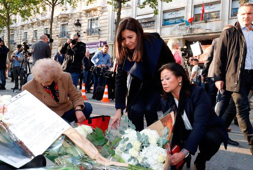 Mayor of Paris Anne Hidalgo, left, and the Mayor of the 8th arrondissement of Paris Jeanne D'hauteserre lay flowers as they pay their respects to Xavier Jugele, the policeman killed Picture: AFP/Getty