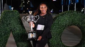 Serena Williams of the US poses with the championship trophy after her victory against Venus Williams of the US in the women's singles final on day 13 of the Australian Open tennis tournament in Melbourne on January 29, 2017. / AFP / SAEED KHAN /AFP/Getty Images)