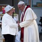 Pope Francis (R) is greeted by Roselyne (L), sister of Father Jacques Hamel, who was killed in Rowen on July 18, 2016 as he leads a mass at the Basilica of Saint Bartholomew on Tiber island in Rome