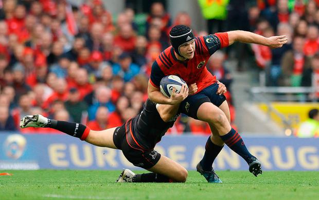 Munster's Tyler Bleyendaal is tackled by Saracens' Richard Wigglesworth. Photo: PA