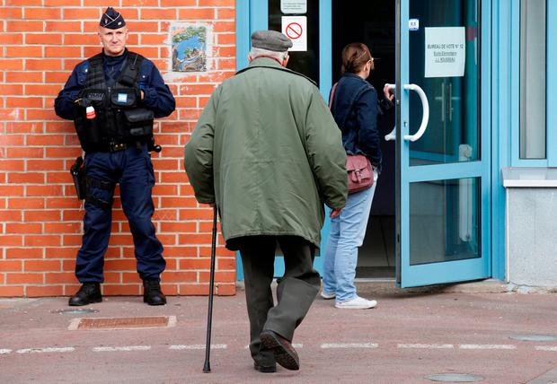 A policeman secures the entrance of a polling station as people arrive to vote in the first round of 2017 French presidential election in Henin-Beaumont, France, April 23, 2017. REUTERS/Pascal Rossignol