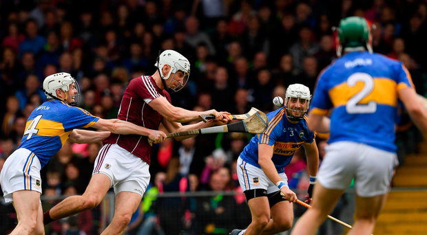 Jason Flynn of Galway has eyes only for the ball as he holds off Tipperary's Michael Cahill (left) before rifling home Galway's second goal Photo by Ray McManus/Sportsfile
