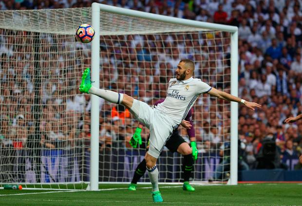Real Madrid's Karim Benzema tries to keep the ball in play. Photo: Reuters