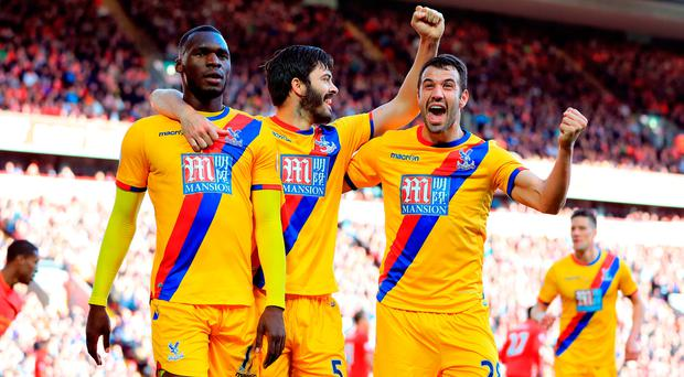 Christian Benteke celebrates scoring the winner with his Palace team-mates at Anfield. Photo: PA