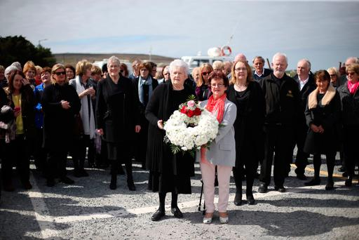 Vera Cusack and Bernie Naughton lay a wreath for the crew of Rescue 116 at the helipad in Blacksod Harbour in Co Mayo. Photos: PA