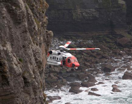 The Rescue 115 helicopter hovers close to the base of the Cliffs of Moher during the operation to recover Malcolm Rowley. Photo Press 22