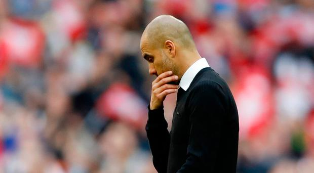 Manchester City manager Pep Guardiola looks dejected after the defeat to Arsenal