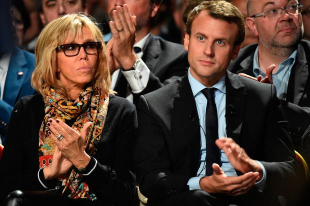 Former French Economy Minister Emmanuel Macron and his wife Brigitte applaud a speech during a meeting of his political movement, 'En Marche' (On the Move), on October 11, 2016 in Le Mans, northwestern France. / AFP / JEAN-FRANCOIS MONIER (Photo credit should read JEAN-FRANCOIS MONIER/AFP/Getty Images)