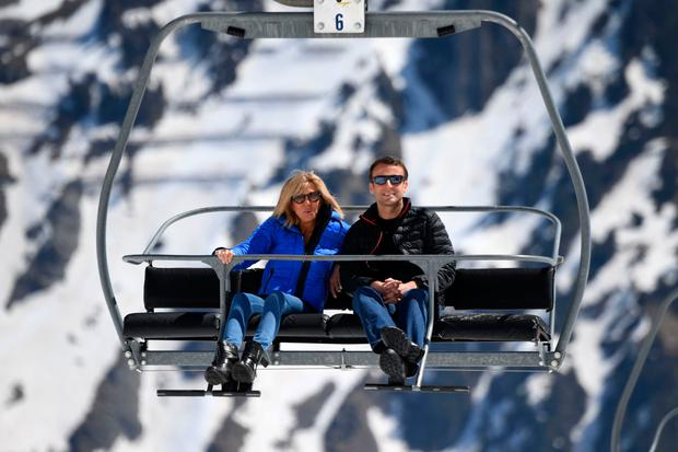 French presidential election candidate for the En Marche ! movement Emmanuel Macron (R) and his wife Brigitte Trogneux sit on a chairlift on their way to the mountain top for a lunch break during a campaign visit in Bagneres de Bigorre on April 12, 2017. / AFP PHOTO / POOL / Eric FEFERBERG (Photo credit should read ERIC FEFERBERG/AFP/Getty Images)