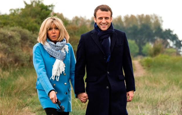 French presidential election candidate for the En Marche ! movement Emmanuel Macron (R) and his wife Brigitte pose for the photograph, on April 22, 2017, in Le Touquet, northern France, on the eve of the first round of presidential election