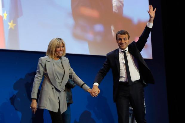 French presidential election candidate for the En Marche ! movement Emmanuel Macron (R) and his Brigitte Trogneux react during a meeting at the Parc des Expositions in Paris, on April 23, 2017, after the first round of the Presidential election. / AFP PHOTO / Patrick KOVARIK (Photo credit should read PATRICK KOVARIK/AFP/Getty Images)