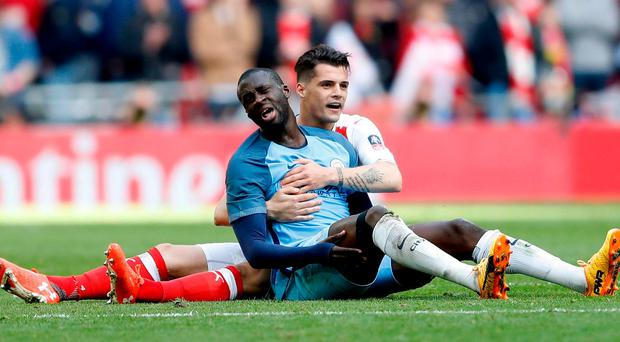 Arsenal's Granit Xhaka and Manchester City's Yaya Toure on the floor yesterday