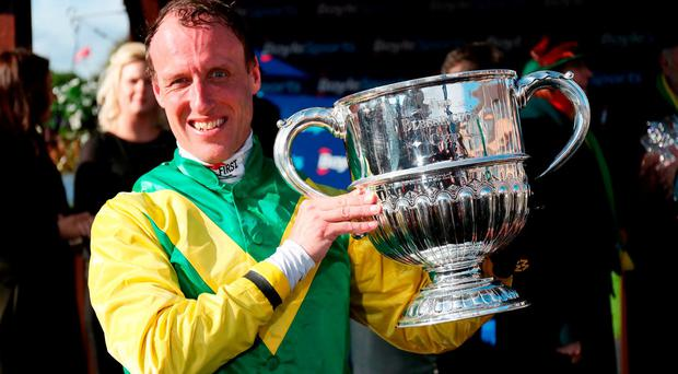 Jockey Robbie Power celebrates with the trophy after riding Fox Norton to victory in the BoyleSports Champion Chase during day one of the Punchestown Festival