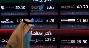 An investor walks past a screen displaying stock information at the Saudi Stock Exchange (Tadawul) in Riyadh, Saudi Arabia