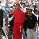 Brazilian footballer Bruno Fernandes de Souza (in red) is taken under custody to the presidium of Belo Horizonte, Brazil, on July 9, 2010. AFP PHOTO/Domingos Peixoto/Agência o Globo- BRAZIL OUT
