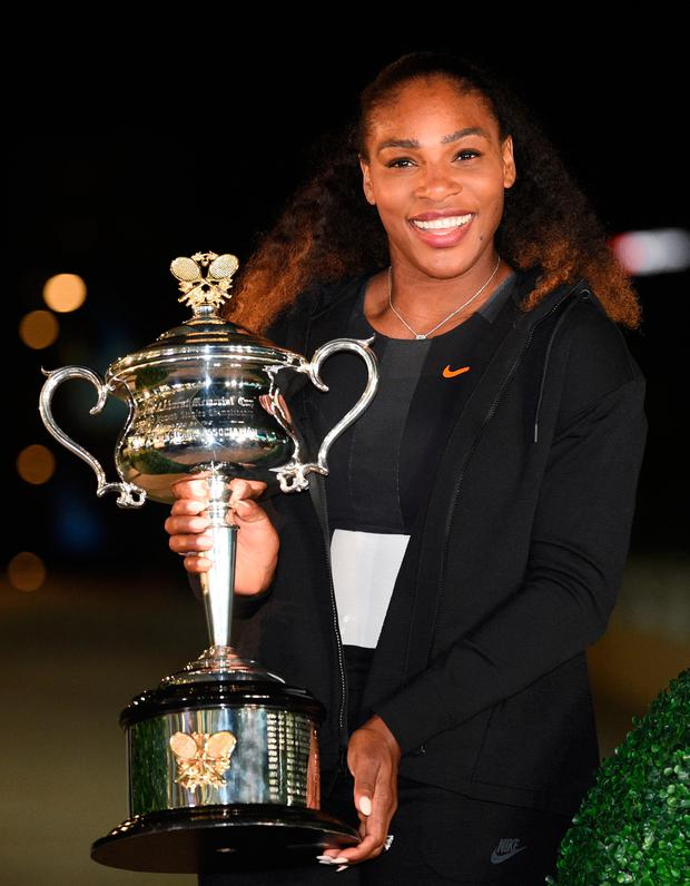 Serena Williams of the US poses with the championship trophy after her victory against Venus Williams of the US in the women's singles final on day 13 of the Australian Open tennis tournament in Melbourne
