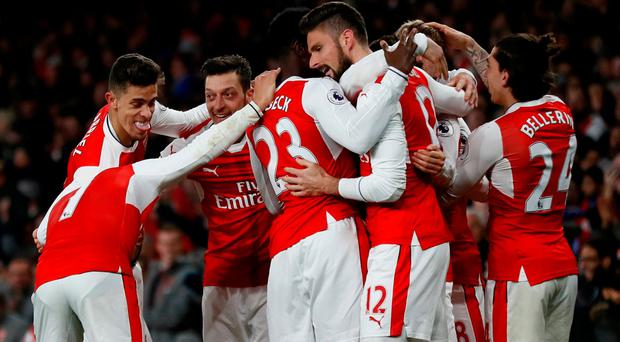 Arsenal's players celebrate after Leicester City's Robert Huth scores an own goal