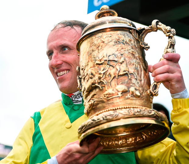 Robbie Power holds the Punchestown Gold Cup after victory aboard Sizing John. Photo: Sportsfile