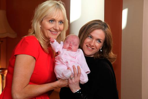 Miriam O'Callaghan and Dr Rhona Mahony holding baby Ariane Cooke, daughter of model agent Jules Fallon, in 2012