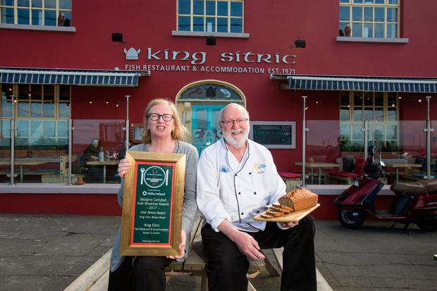 Aidan with his wife Joan outside their restaurant and guest house in Howth. Photo: Mark Condren