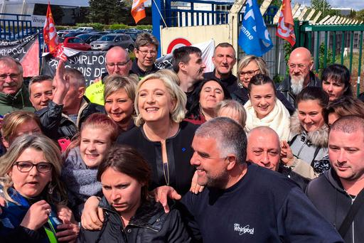 French presidential election candidate Marine Le Pen smiles with workers in front of the threatened Whirlpool factory in Amiens, in northern France. Photo: AFP