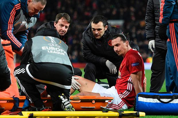 Manchester United's Swedish striker Zlatan Ibrahimovic gets treatment after injuring his knee