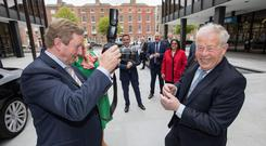 Taoiseach Enda Kenny turns the camera on Irish Independent photographer Tom Burke at the formal opening of Shire's new corporate HQ in Miesian Plaza, Baggot Street, Dublin. Photo: Naoise Culhane
