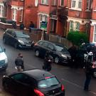 A woman is surrounded by police while being treated at the scene in Harlesden Road, north London. Photo credit: PA/PA Wire