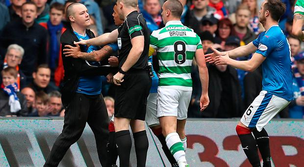 Fan invades the pitch as Celtic's Scott Brown looks on before the game