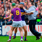Wexford manager Davy Fitzgerald tussles with Tipperary's Jason Forde at Nowlan Park. Photo: Ramsey Cardy/Sportsfile