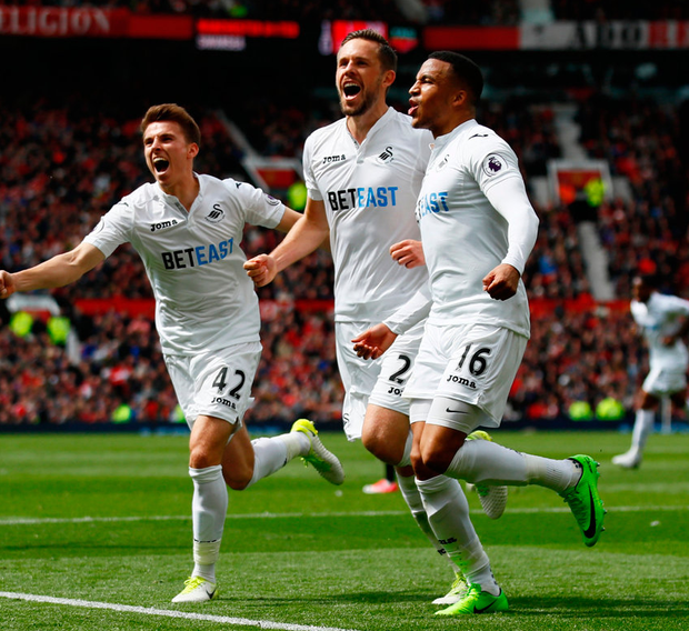 Swansea City's Gylfi Sigurdsson celebrates with Tom Carroll and Martin Olsson after scoring their side's goal. Photo: Jason Cairnduff/Reuters