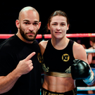 Katie Taylor celebrates with trainer Ross Enamait following her Super-Featherweight fight with Karina Kopinska at Wembley Arena