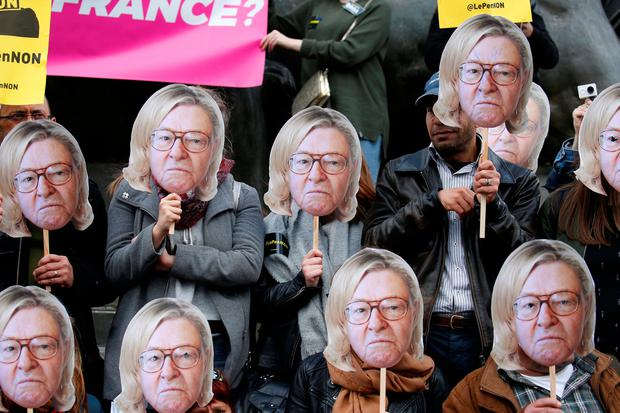 Anti-Front National activists with masks showing Marine Le Pen with her father Jean-Marie's face. Photo: Reuters