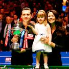 Mark Selby holds the world championship trophy with his daughter Sofia Maria and wife Vikki Layton at the Crucible Theatre. Photo credit: Steven Paston/PA Wire